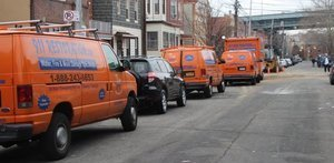 Water Damage Restoration Vans And Trucks Lined Up At Urban Job Location
